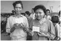 Two Cambodian women in Phnom Penh with voter registration forms in 1992. (CATHERINE KARNOW/CORBIS)